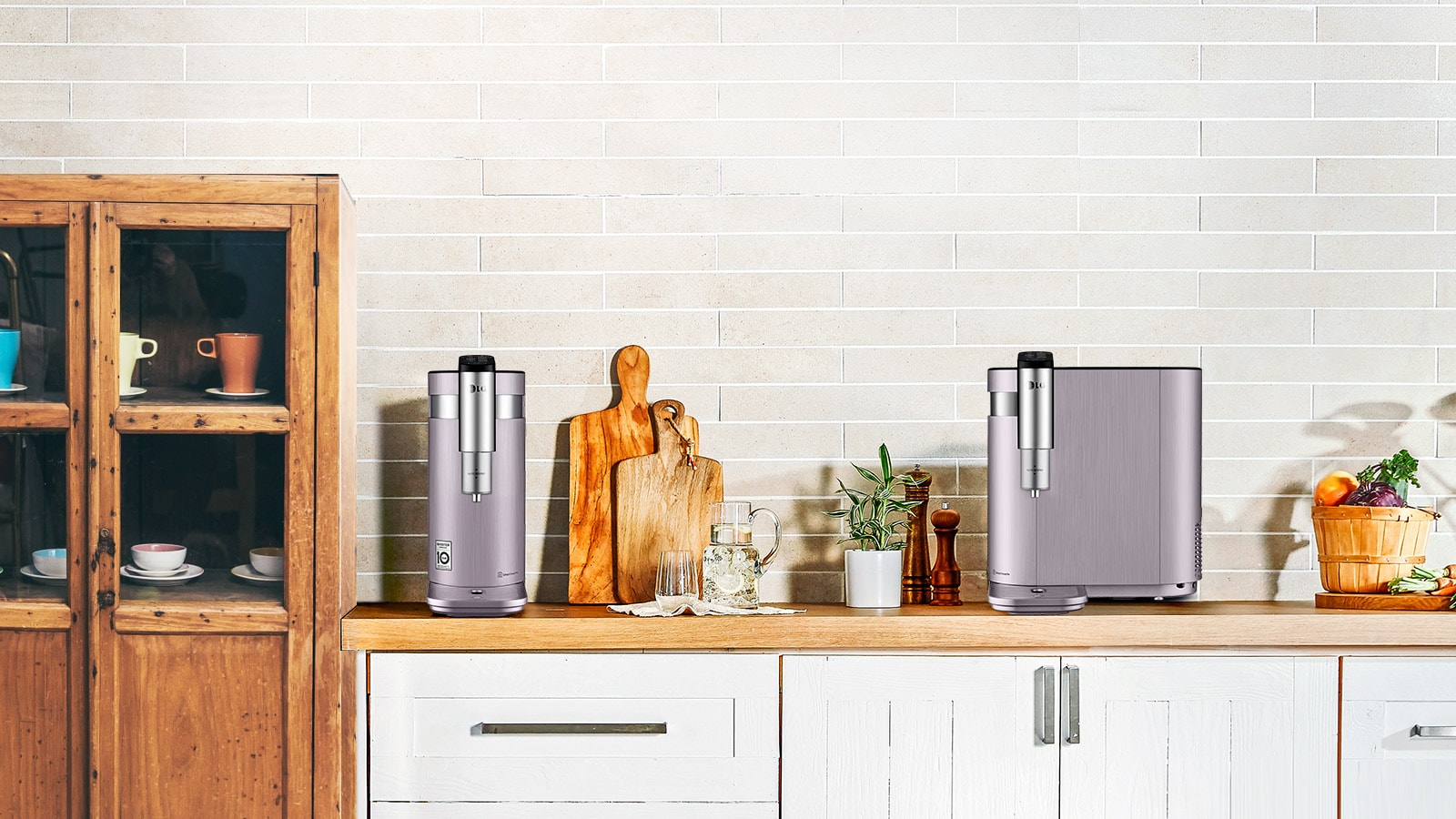 Two water purifiers are shown in a kitchen. One is shown with the thin end forward and the tap on that side. The second is shown with the tap on the longer side to show the possibilities.