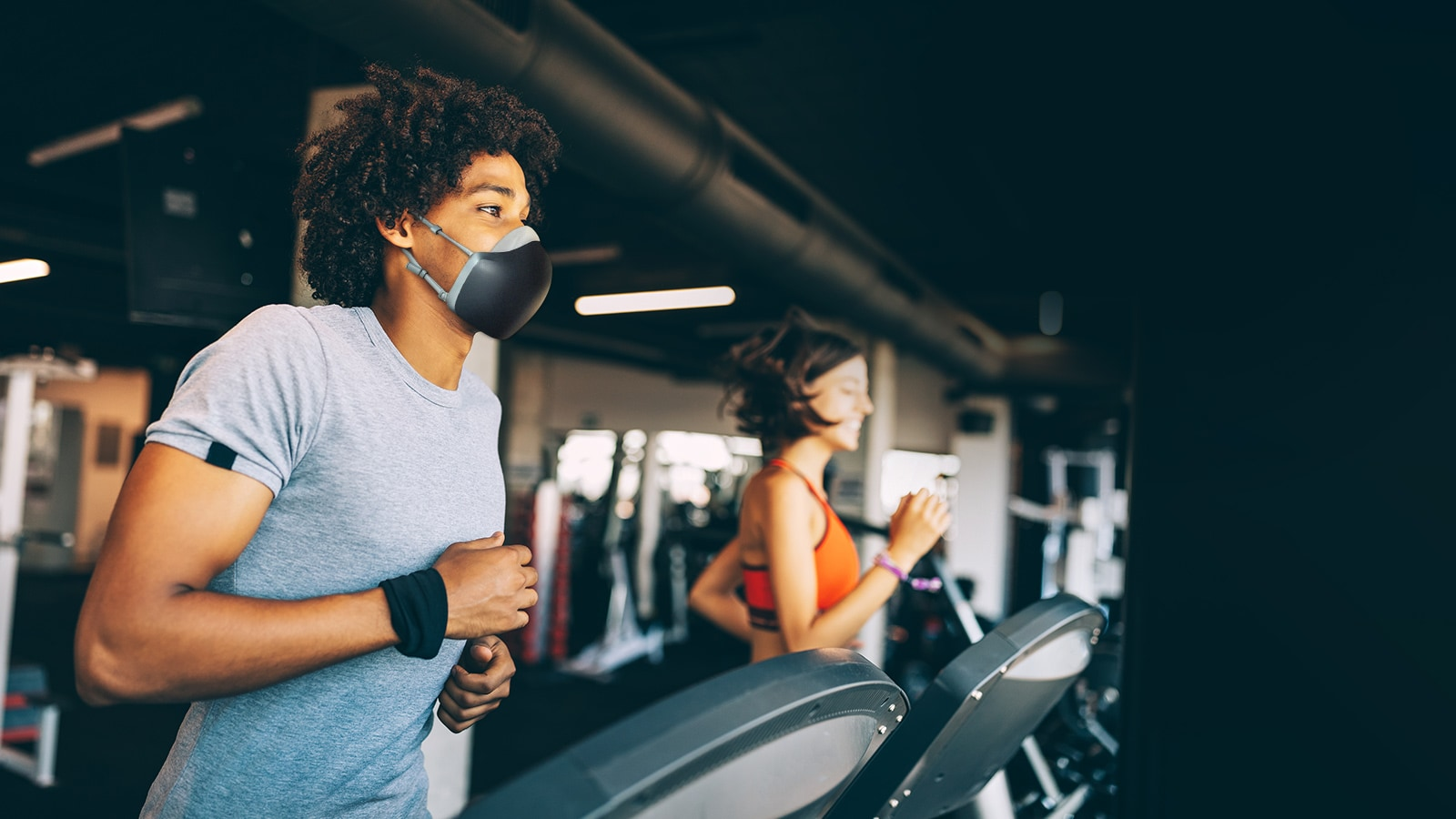 An African American man is running on a treadmill in a gym with the black color LG PuriCare wearable Air Purifier on. He seems like to breathe without breaking a sweat.