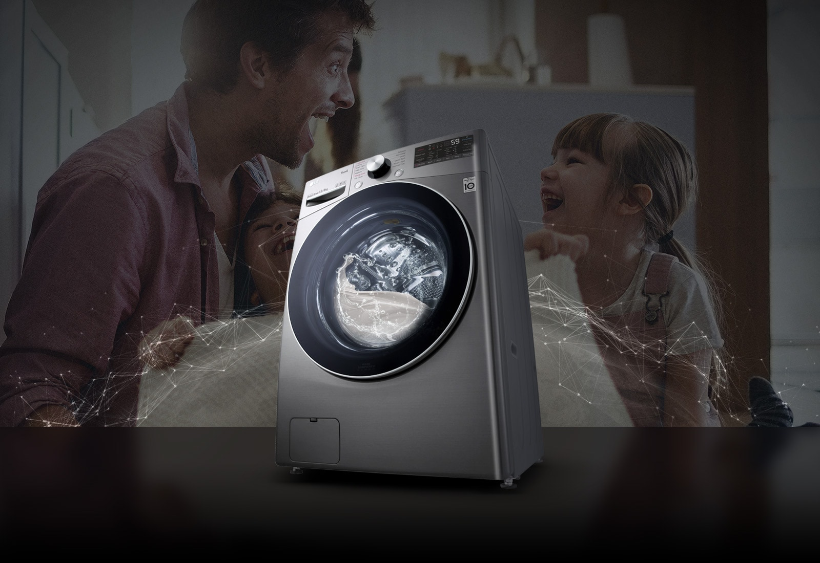 Father and daughters laugh in the background as they hold a clean blanket. A White washing machine front load washer in the foreground.