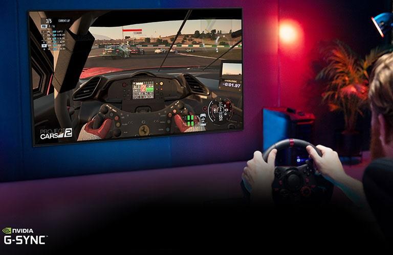 Man zit op een gaming stoel met een racestuur tijdens het spelen van een racespel op een tv-scherm