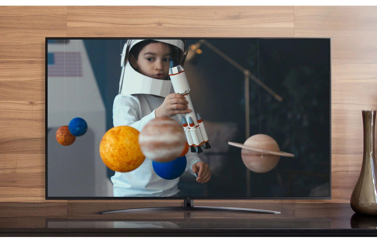 Een tv-scherm speelt een video af van een jongen in een zelfgemaakt astronautenpak die met een ruimteschip speelt in zijn kamer die versierd is met miniaturen van planeten (speel de video af)