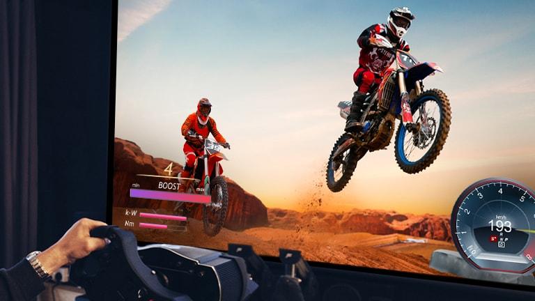 Een close-up van een speler die een motorracegame speelt op een tv-scherm.