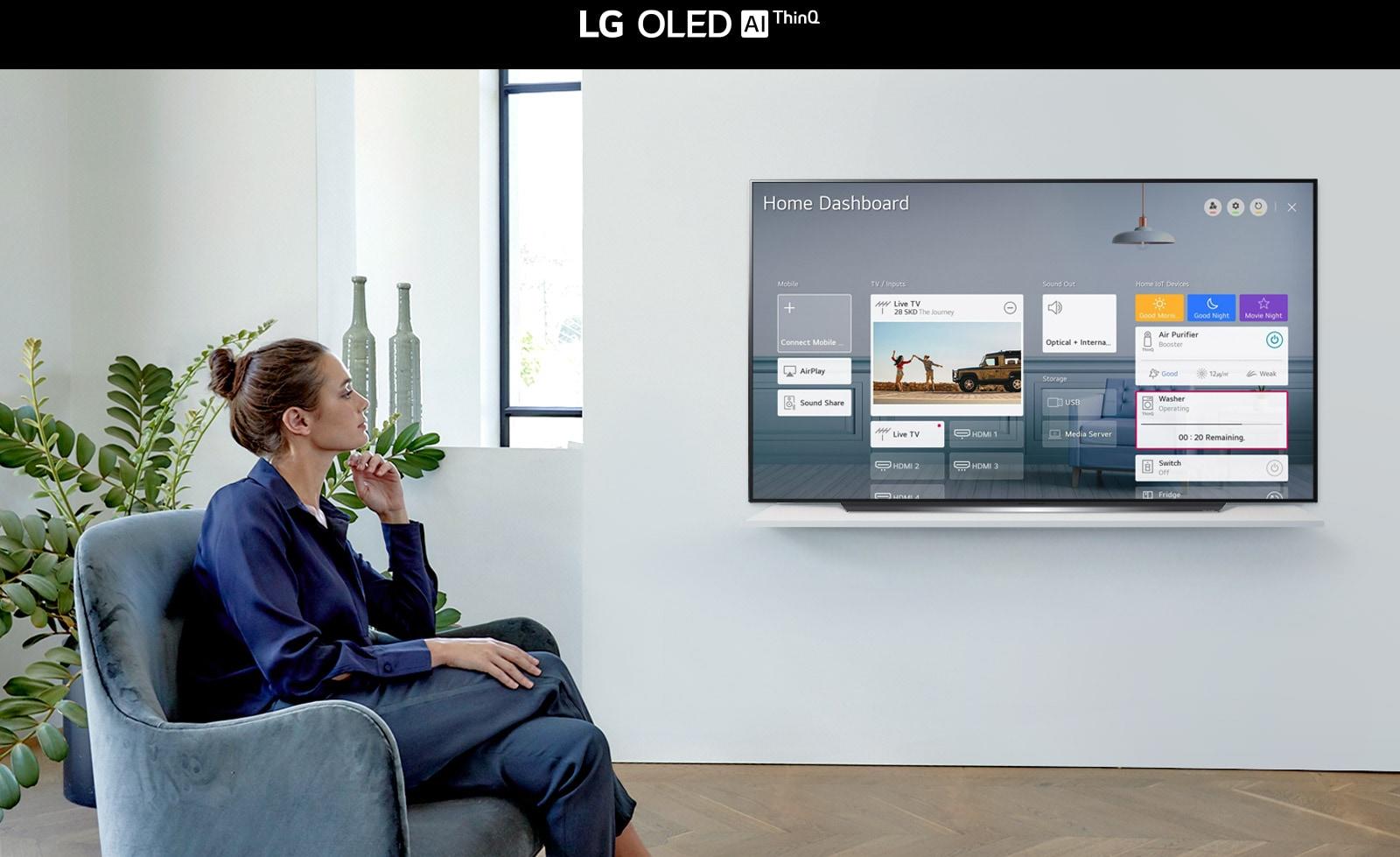 Vrouw zit op een stoel in de woonkamer met het Home Dashboard op het tv-scherm.