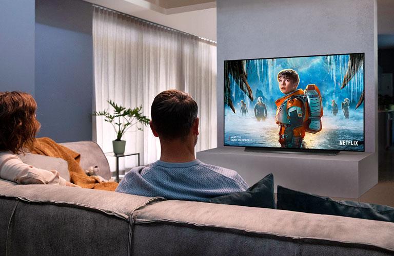 Stelletje zittend op een bank in de woonkamer kijken naar een romantische film op tv
