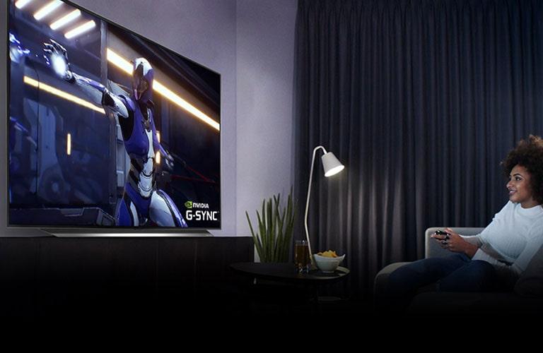 Een tv met een gaming-scène en een pc op een bureau