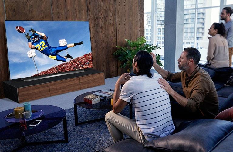 Mensen kijken naar een Tottenham wedstrijd op tv in de woonkamer