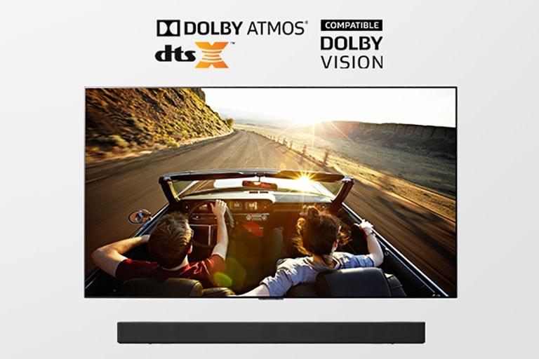 Tv en soundbar samen in beeld. TV toont een koppel onderweg in een cabriolet richting zonsondergang.