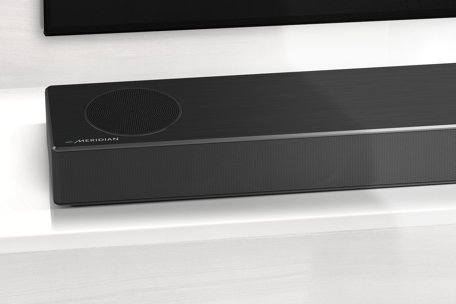 Close-up van LG Soundbar linksonder met Meridian-logo in de linkerbenedenhoek. Linksonder is ook de tv te zien.
