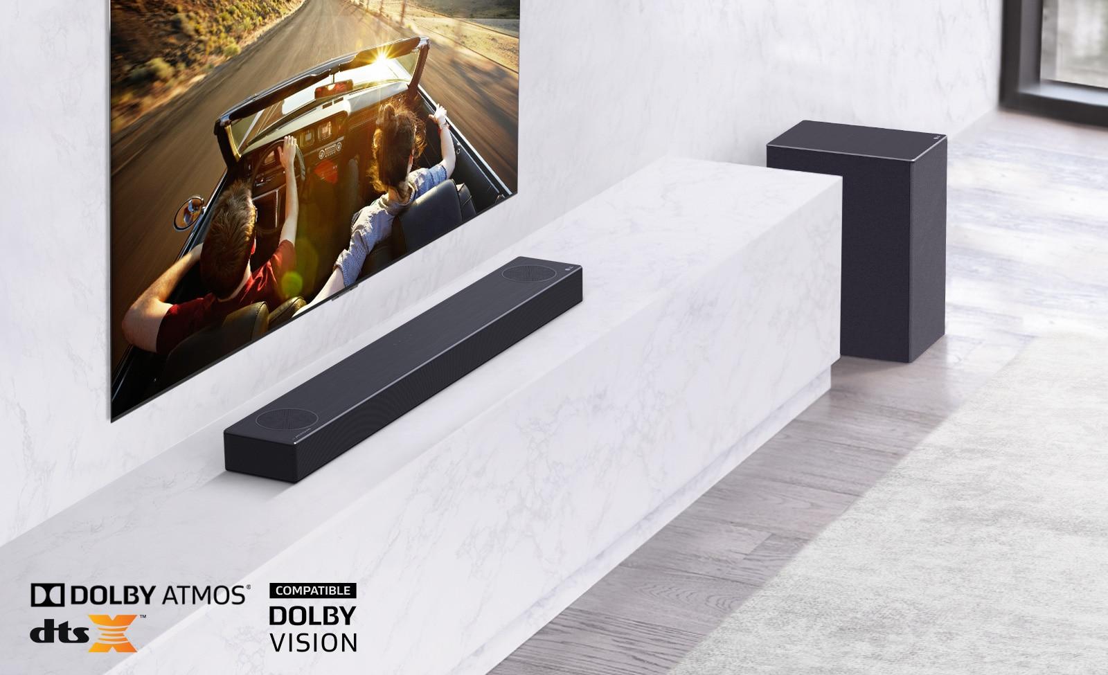 Tv aan de muur, LG Soundbar staat onder op een witte marmeren plank met rechts een subwoofer. Tv toont een koppel in een auto.