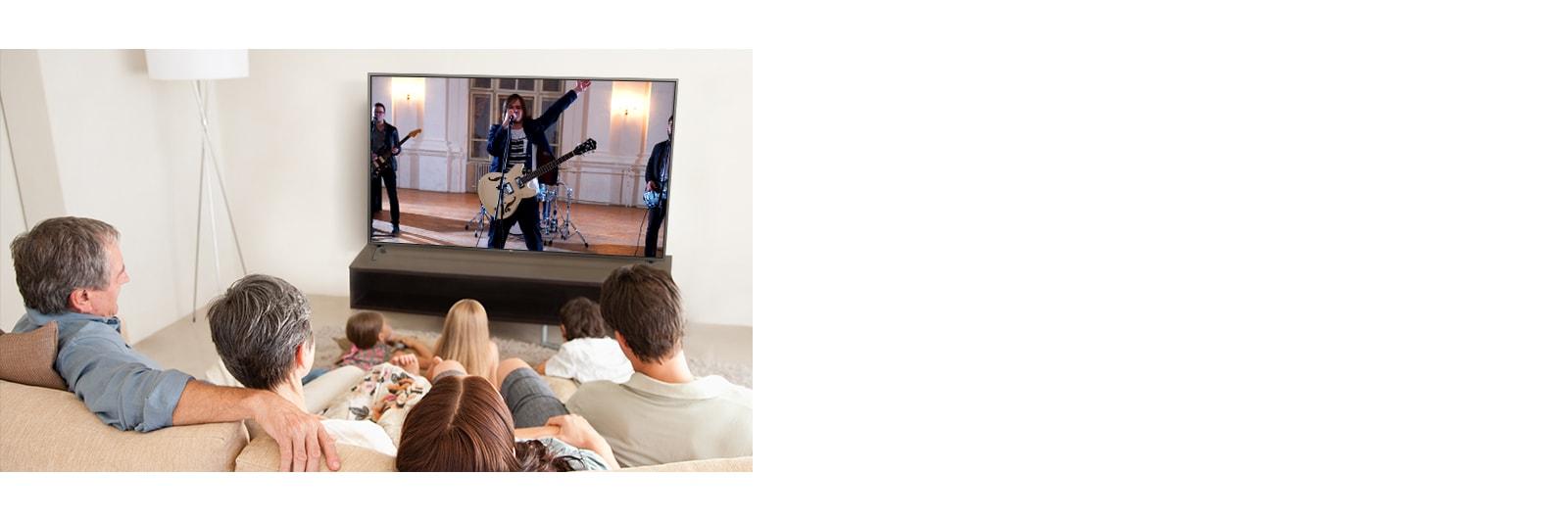 Gezin met zeven mensen die in de woonkamer naar een film kijken. Op het tv-scherm speelt een band.