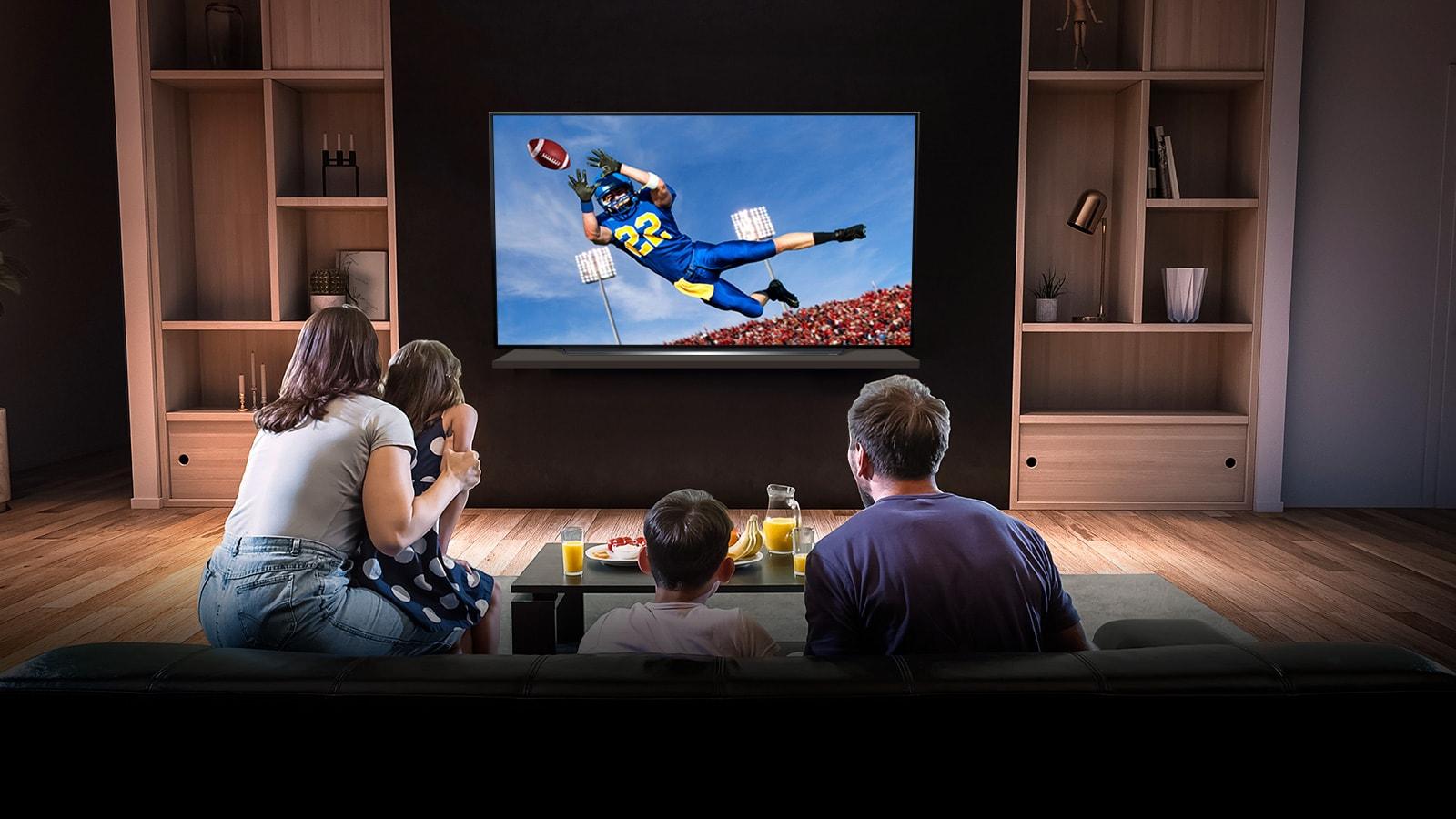 Personas mirando un partido de fútbol americano en la TV de la sala de estar
