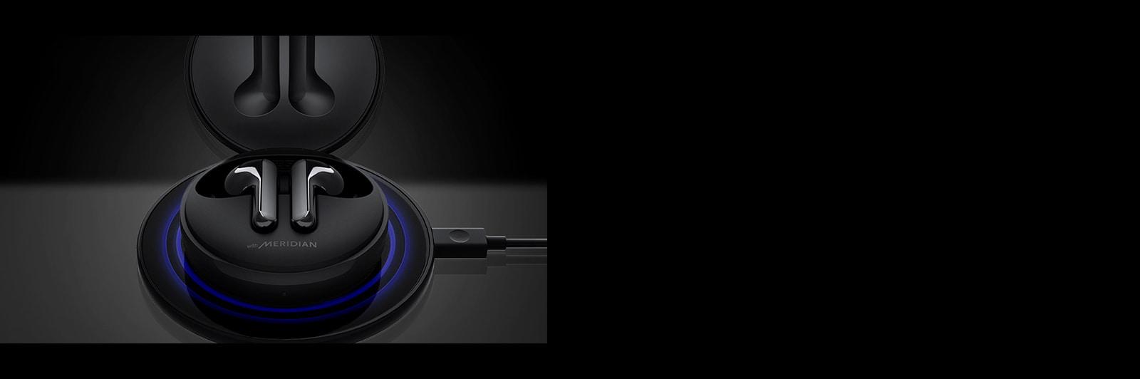 Una imagen de un LG Tone Free FN6 abierto y cargándose en una base de carga inalámbrica negra con iluminación azul.