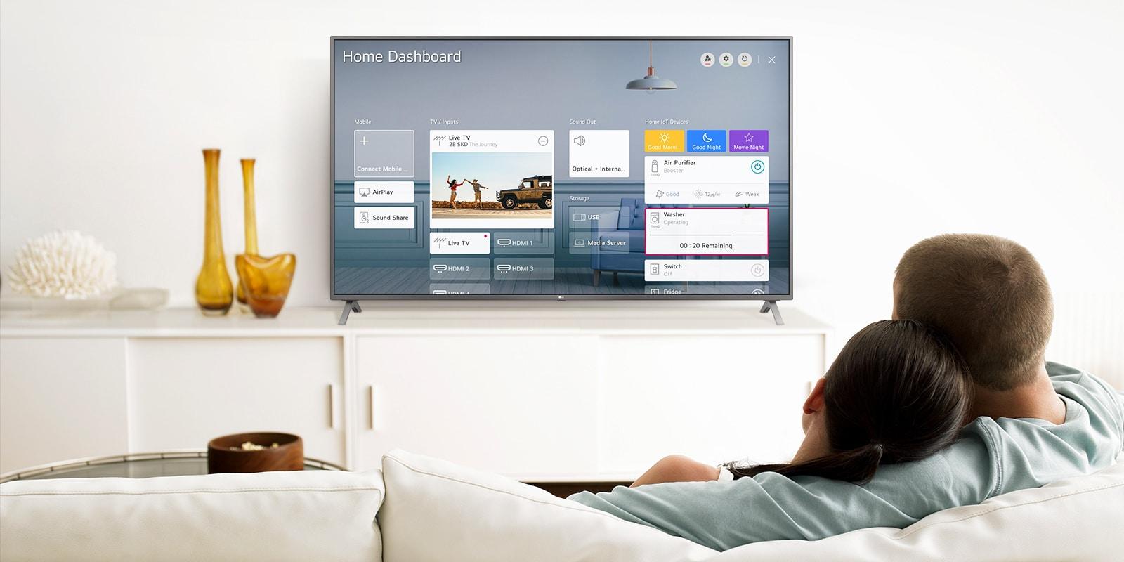 Một người đàn ông và một người phụ nữ ngồi trên ghế sofa trong phòng khách với Bảng điều khiển Home trên màn hình TV.
