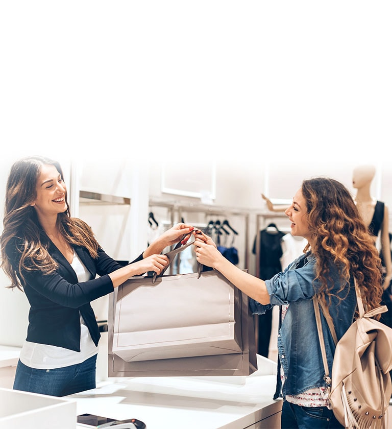 An Image of a sales clerk smiling and giving a customer shopping bags in a clothing store.