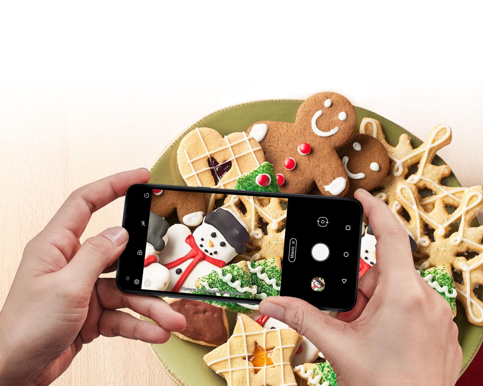 Zbliżenie osoby trzymającej smartfon i robiącej zdjęcie ciastek