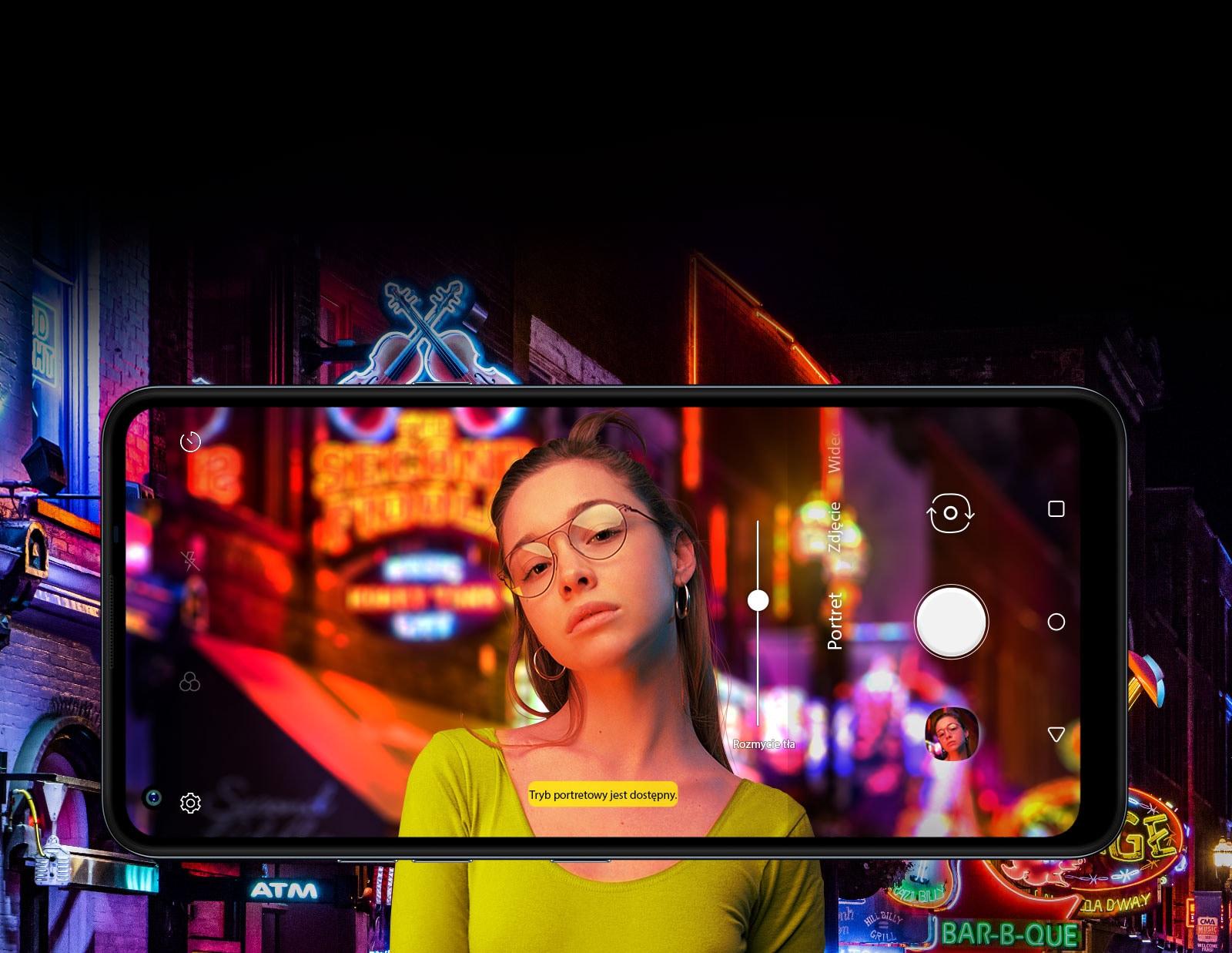 Kobieta robiąca selfie na tle ulicy, wzdłuż której ustawione są neony