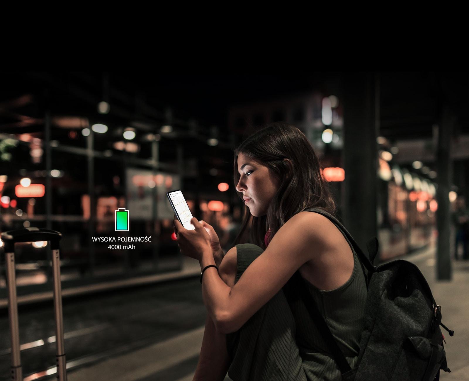 Kobieta przeglądająca internet na smartfonie późno w nocy na stacji metra z dużym  zapasem  energii w baterii
