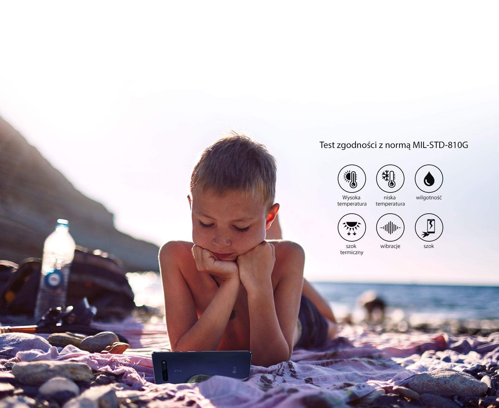 Dziecko leżące na plaży i oglądające film na smartfonie