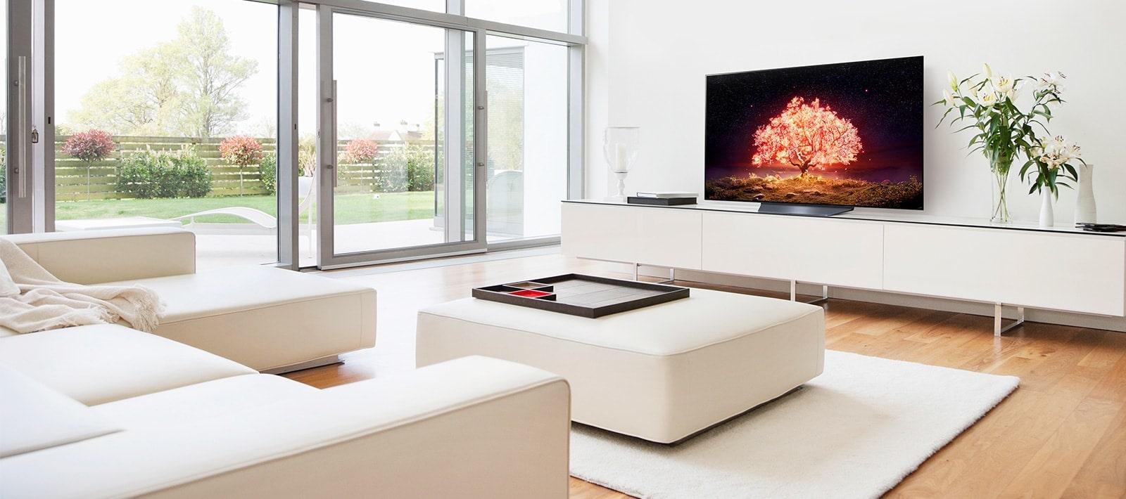 Telewizor przedstawiający drzewo emitujące czerwone światło w białym i prosto urządzonym wnętrzu domu.