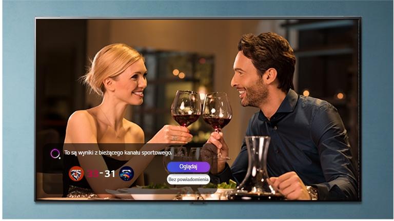 Mężczyzna i kobieta stukający się kieliszkami na ekranie telewizora, na którym pojawia się powiadomienie sportowe