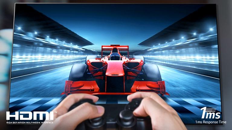 Zbliżenie na gracza grającego w grę wyścigową na ekranie telewizora. W lewym dolnym rogu obrazu znajduje się logo HDMI, a w prawym dolnym rogu – 1ms czasu reakcji.