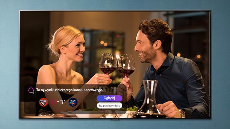 Mężczyzna i kobieta stukający się kieliszkami na ekranie telewizora, na którym wyświetlone jest powiadomienie sportowe