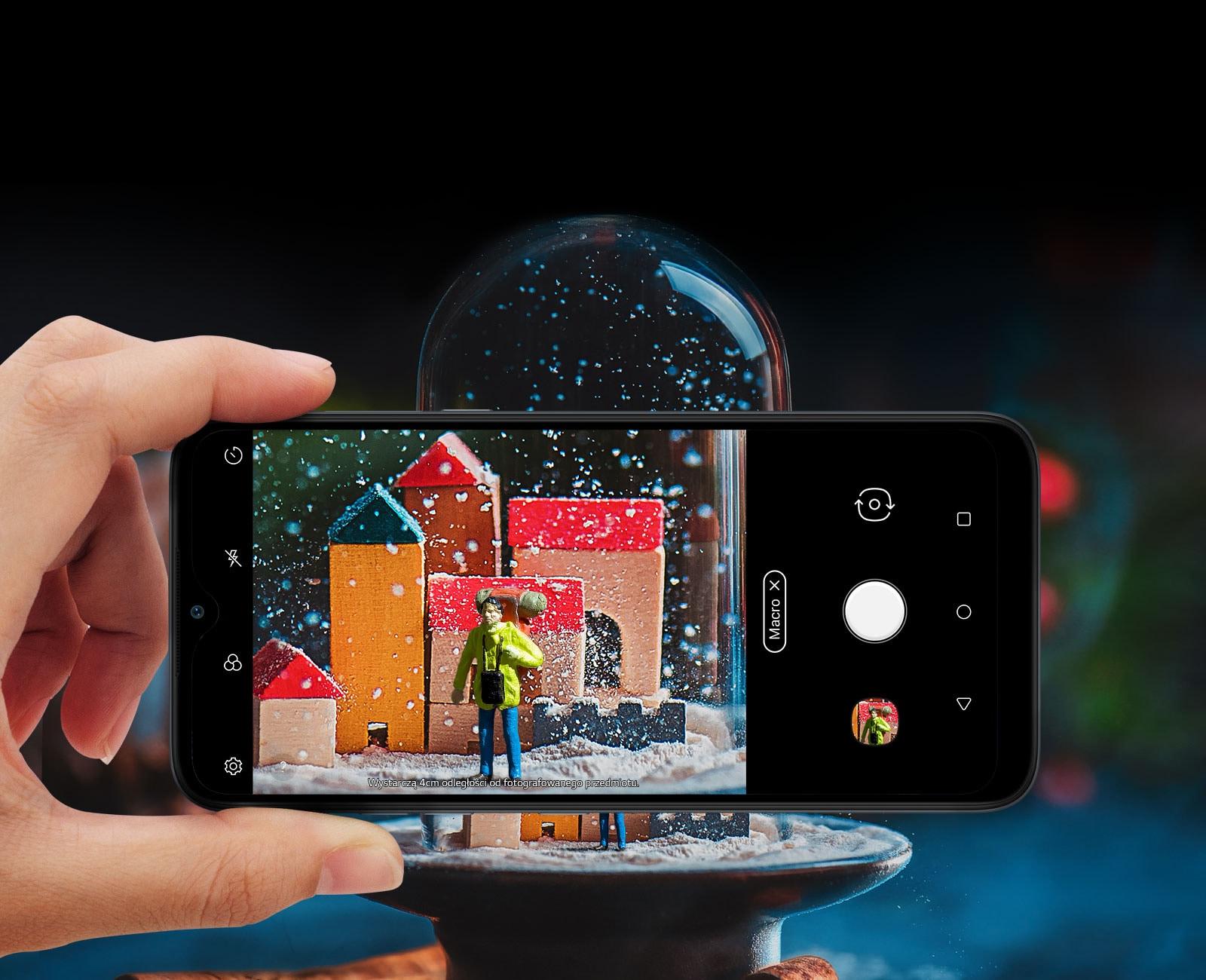 Zbliżenie osoby trzymającej smartfon i robiącej zdjęcie kuli śnieżnej