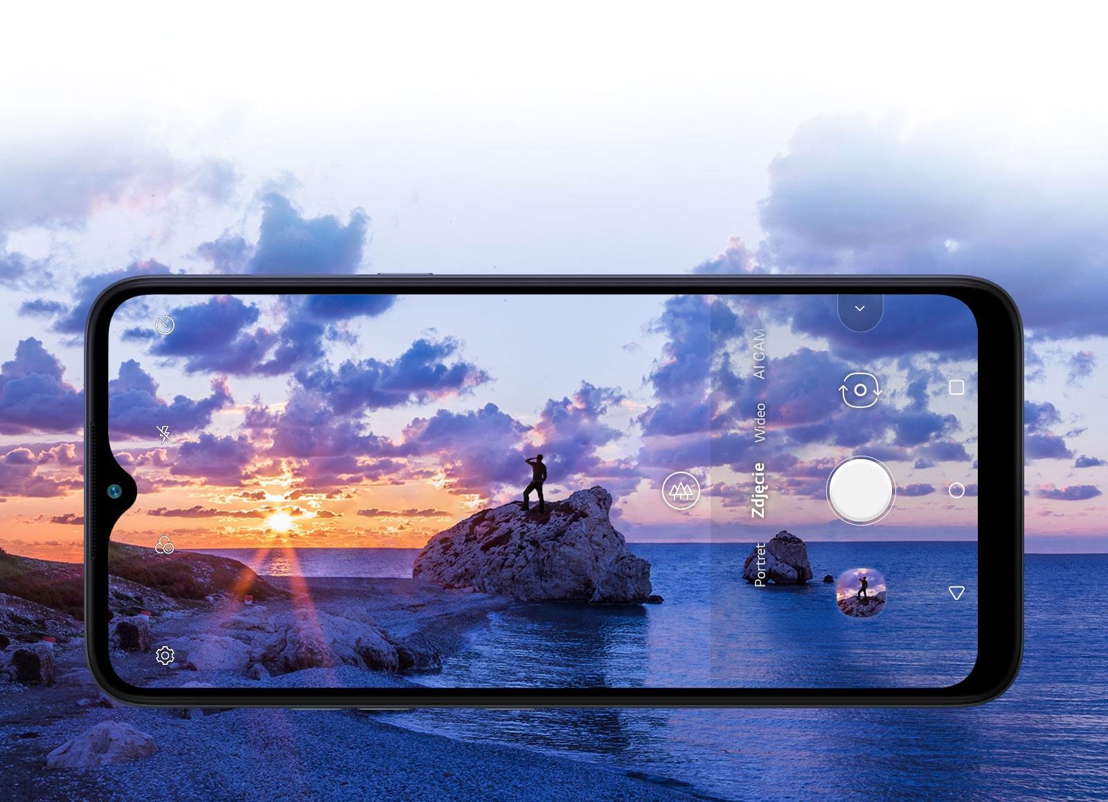 Smartfon fotografujący mężczyznę oglądającego zachód słońca na plaży