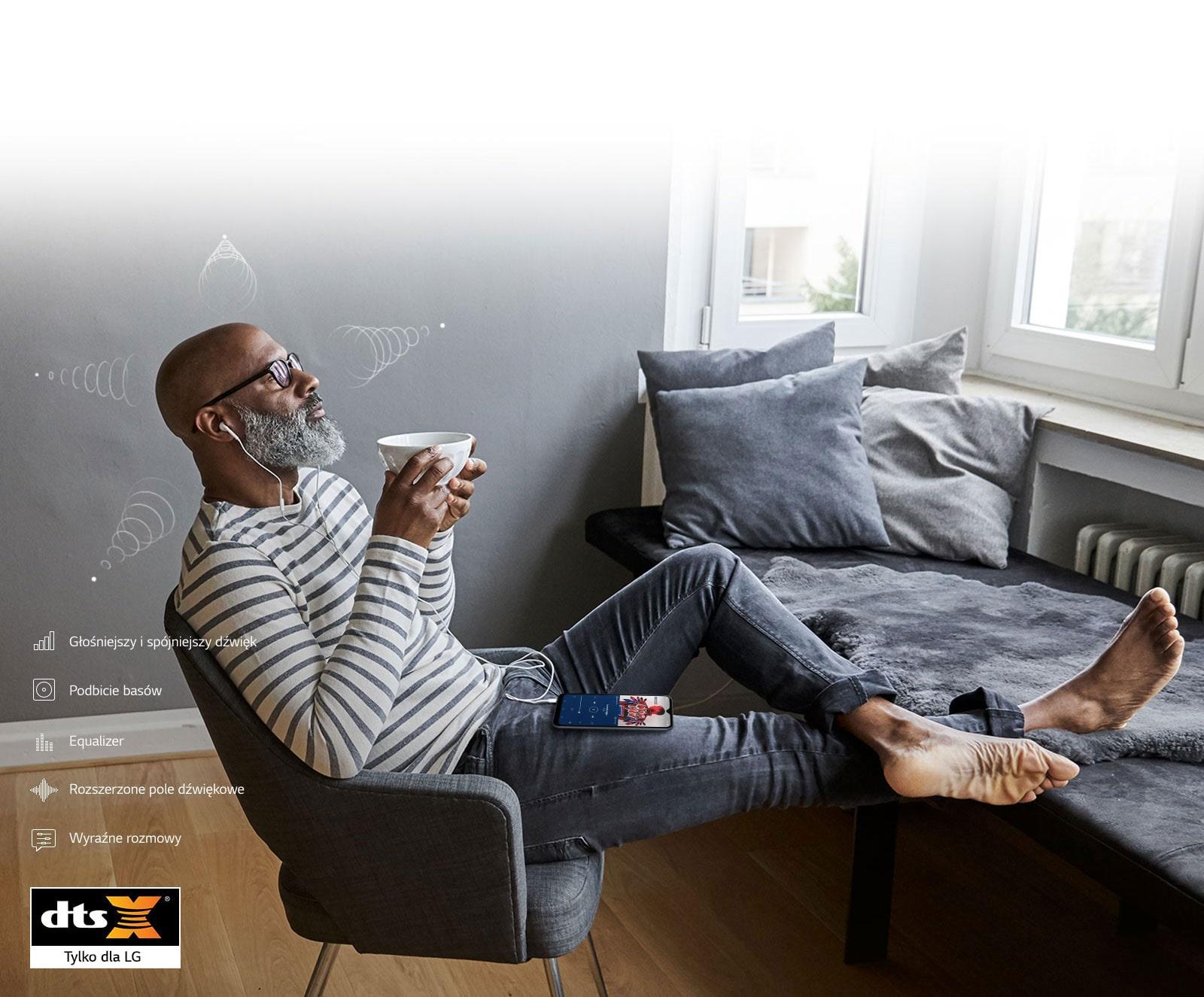 Mężczyzna siedzący na krześle, popijający kawę i słuchający muzyki na słuchawkach