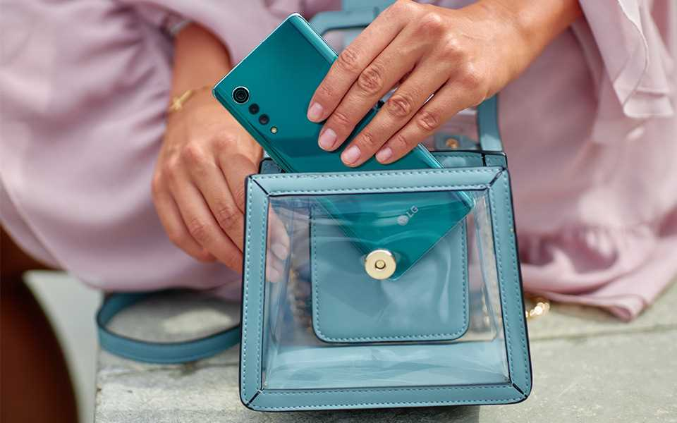 A woman is putting an LG VELVET smartphone in her bag.