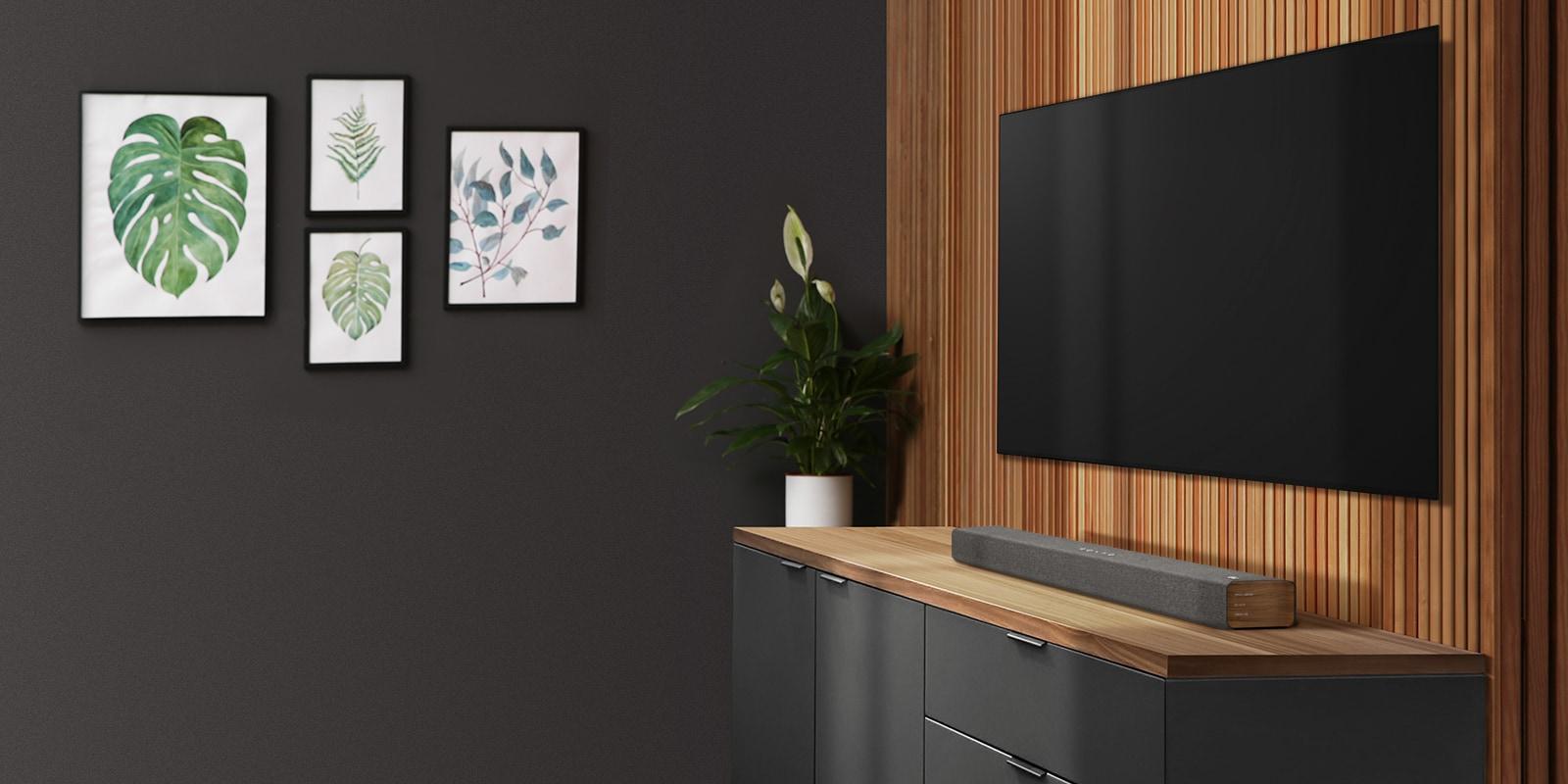 A TV e a barra de som numa parede em madeira. Há quatro molduras numa parede escura.