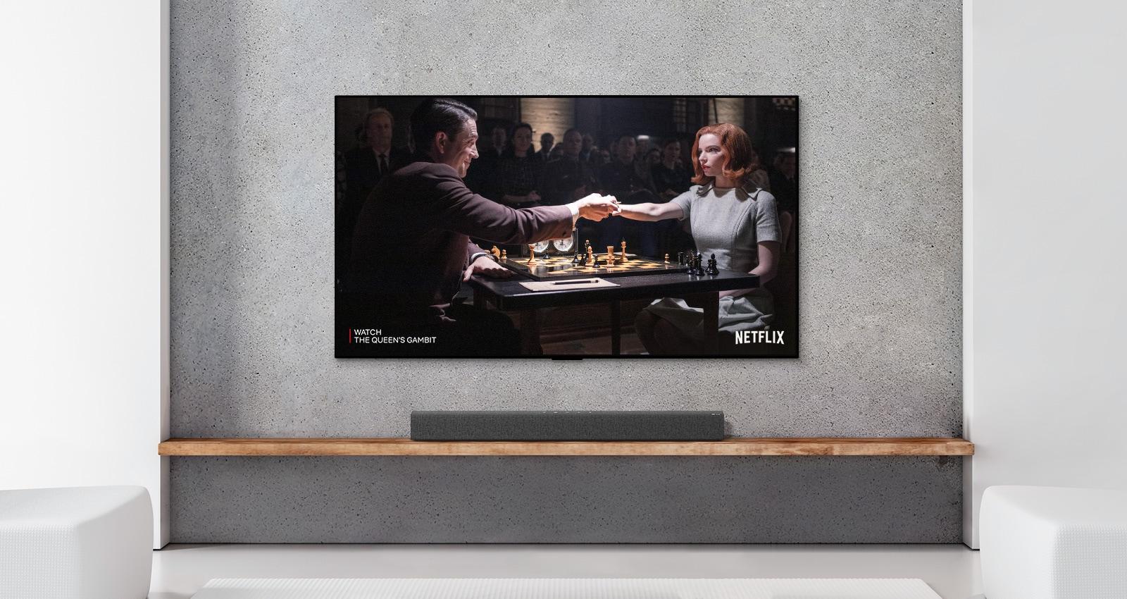 Uma barra de som e TV numa sala branca. Um casal joga xadrez no ecrã da TV.