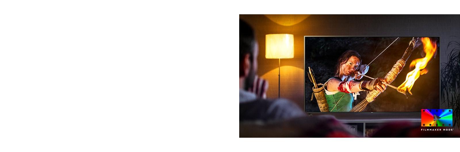 Čovek sedi na kauču i gleda akcioni film. Devojka na televizoru ima potpuno zategnut luk i strelu.