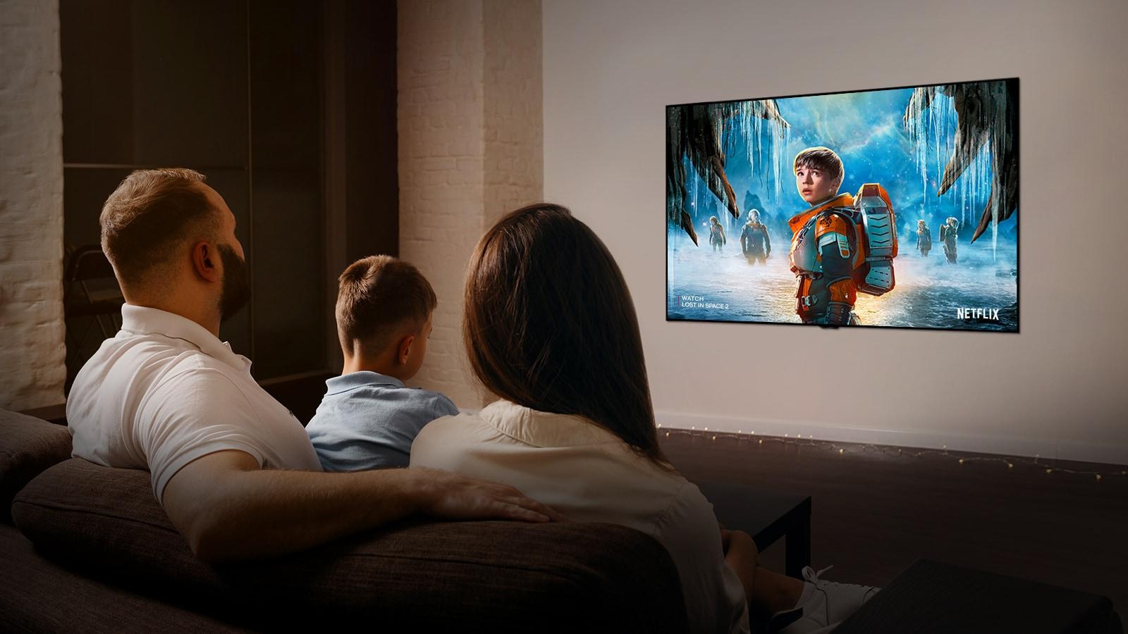 Пара сидит на диване в гостиной и смотрит романтический фильм по телевизору.