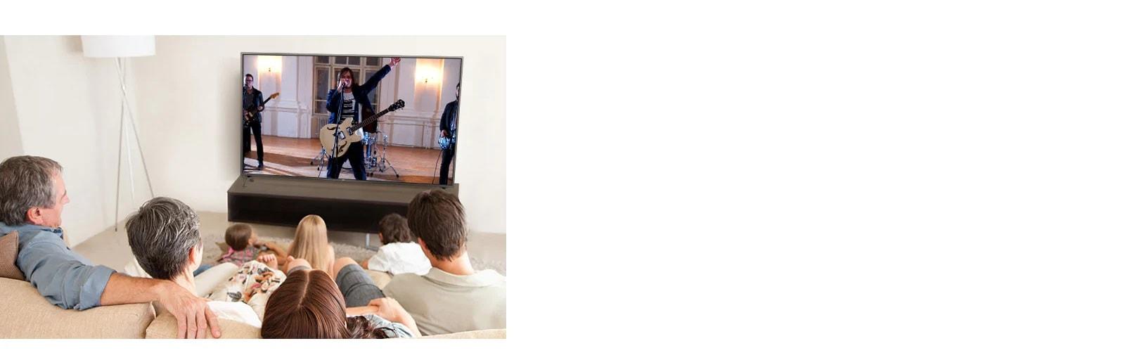 Семья из семи человек находится в гостиной и смотрит фильм. На экране выступает группа музыкантов.
