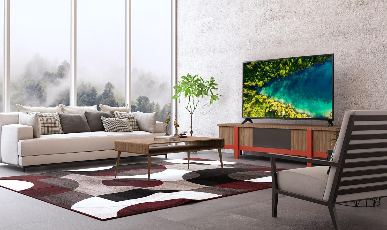 Телевизор, на экране которого показан вид сверху на густой лес, в котором стоит современный и простой дом.