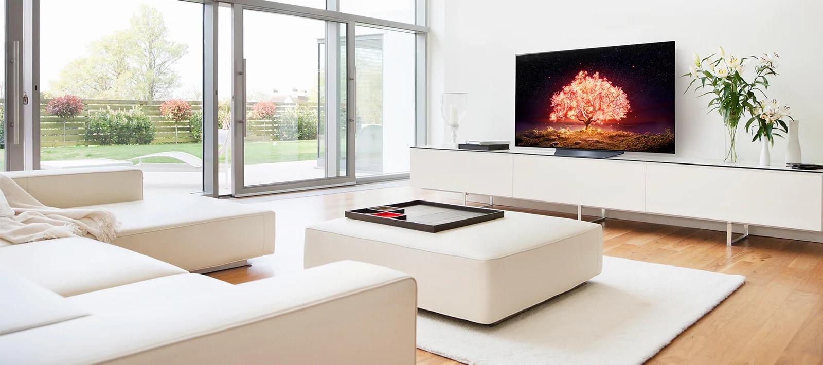 Телевизор, демонстрирующий дерево, излучающее красный свет на белом фоне, и простую обстановку дома