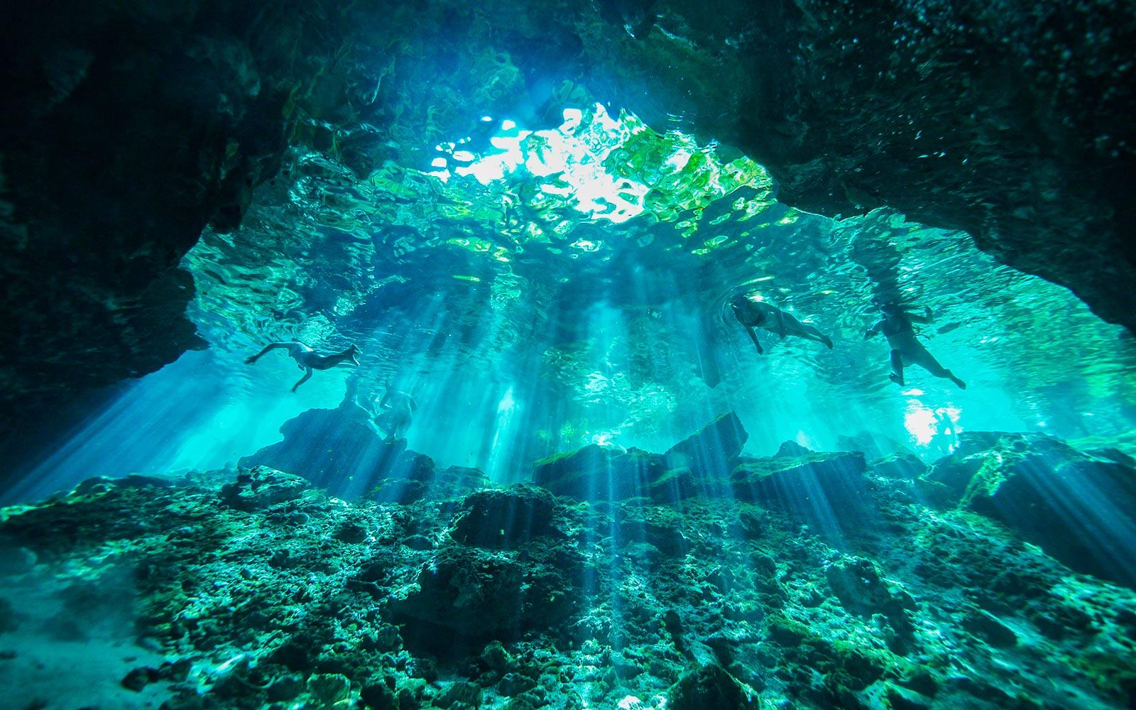 Подводная сцена, освещенная лучами света, падающими в воду (воспроизвести видео).