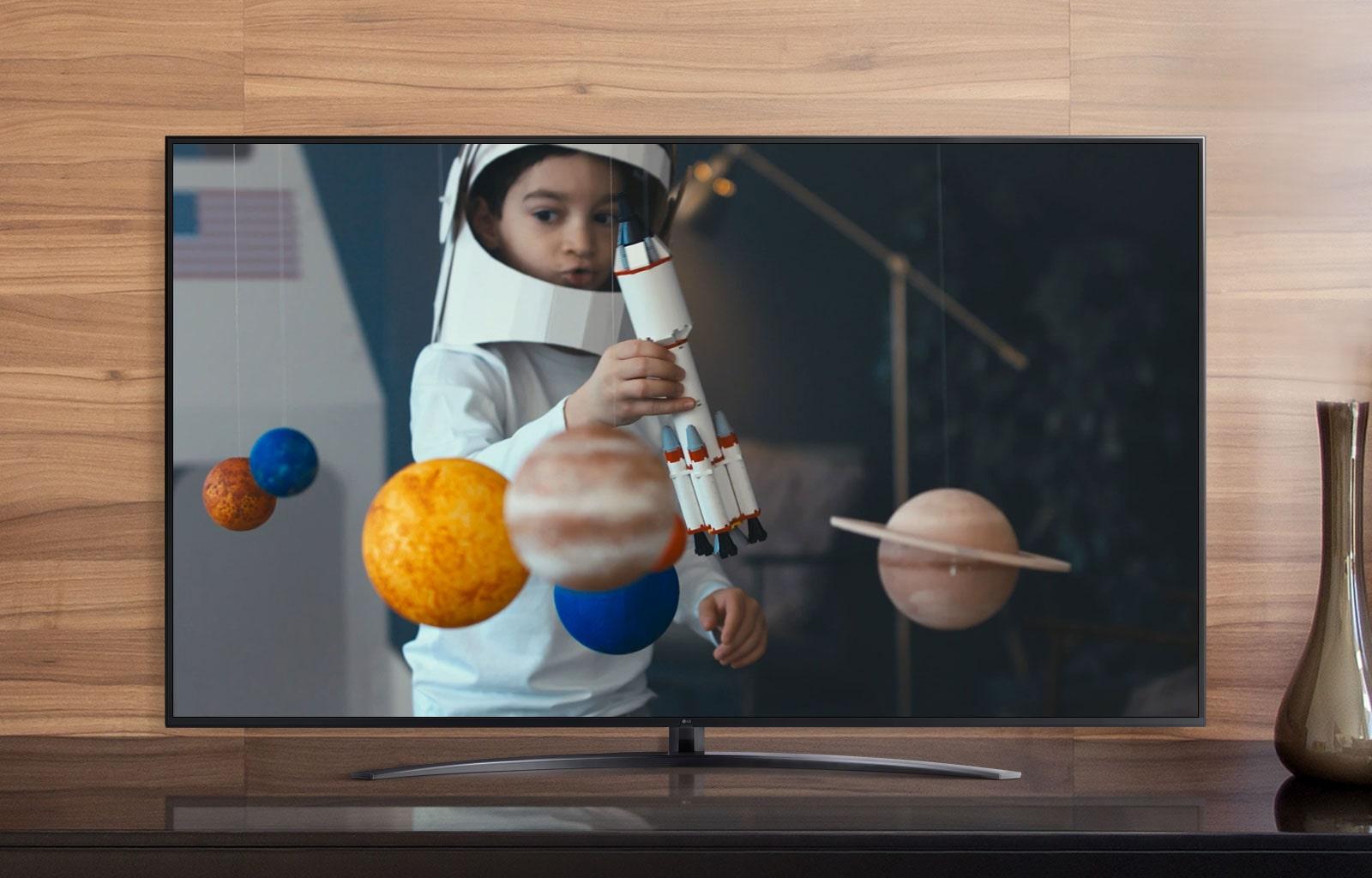 Экран телевизора с мальчиком в самодельном костюме космонавта, играющим с космическим кораблем в комнате, украшенной миниатюрами планет (просмотр видео)