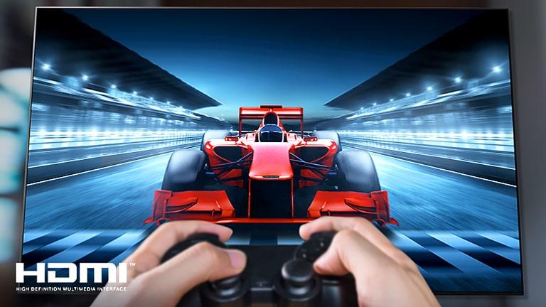 Крупный план геймера, играющего в гоночную игру на экране телевизора. В левой нижней части изображения показан логотип HDMI.