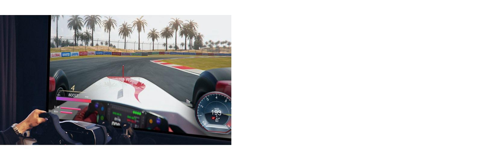 Крупный план игрока, держащего в руках руль и играющего на телевизоре в гонки.