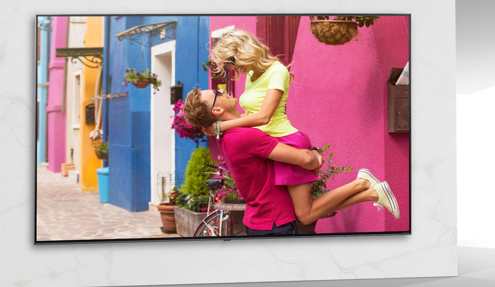 На телеэкране изображена сцена из яркого романтического фильма, где мужчина и женщина обнимаются.