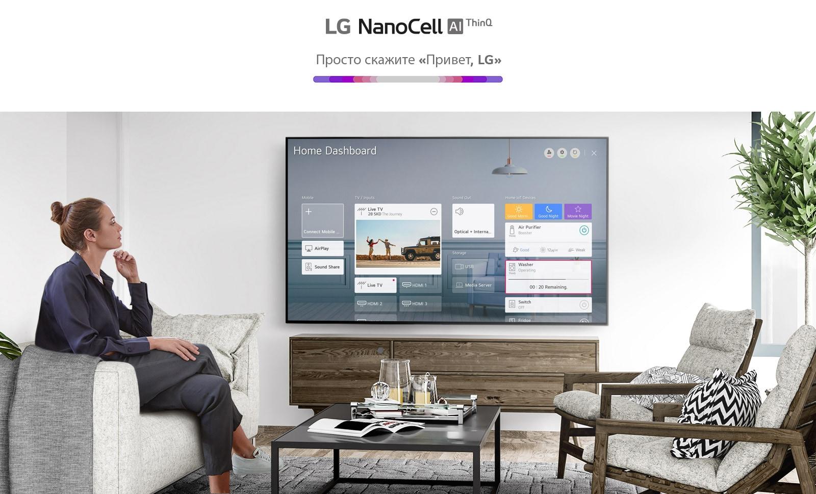 Женщина сидит на диване в гостиной перед телевизором, на котором показана панель управления бытовой техникой.