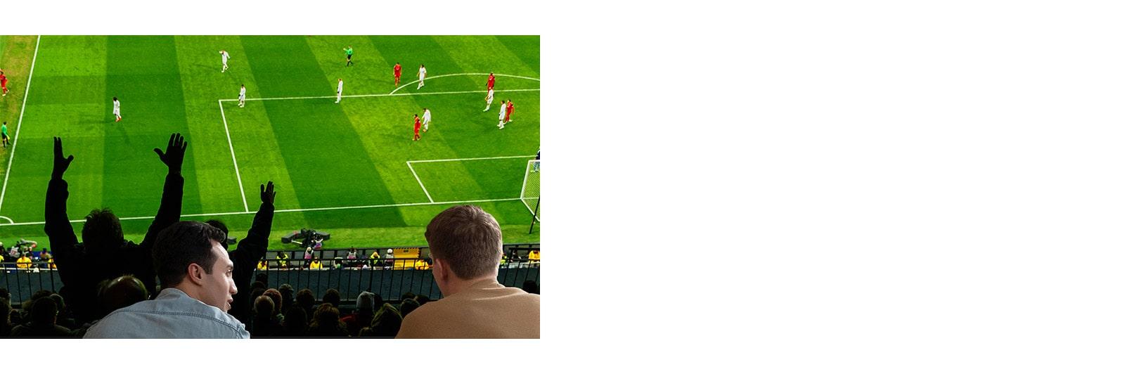 Люди смотрят спортивную игру в гостиной на телевизоре с ультра-большим экраном.