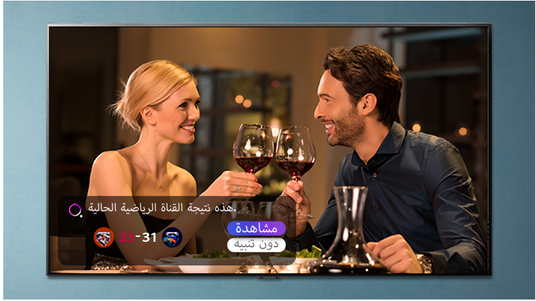 رجل وامرأة ينظران نحو شاشة التلفزيون أثناء ظهور التنبيهات الرياضية