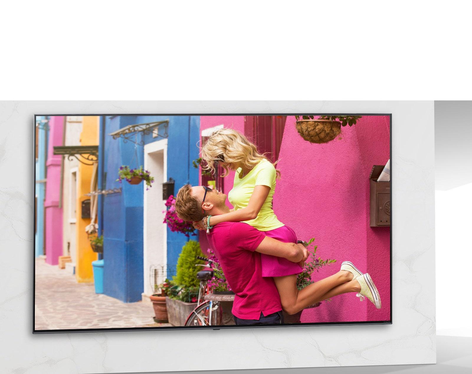 شاشة تلفزيون تعرض أحد المشاهد من فيلم رومانسي ملون يظهر رجلا وامرأة يتعانقان.