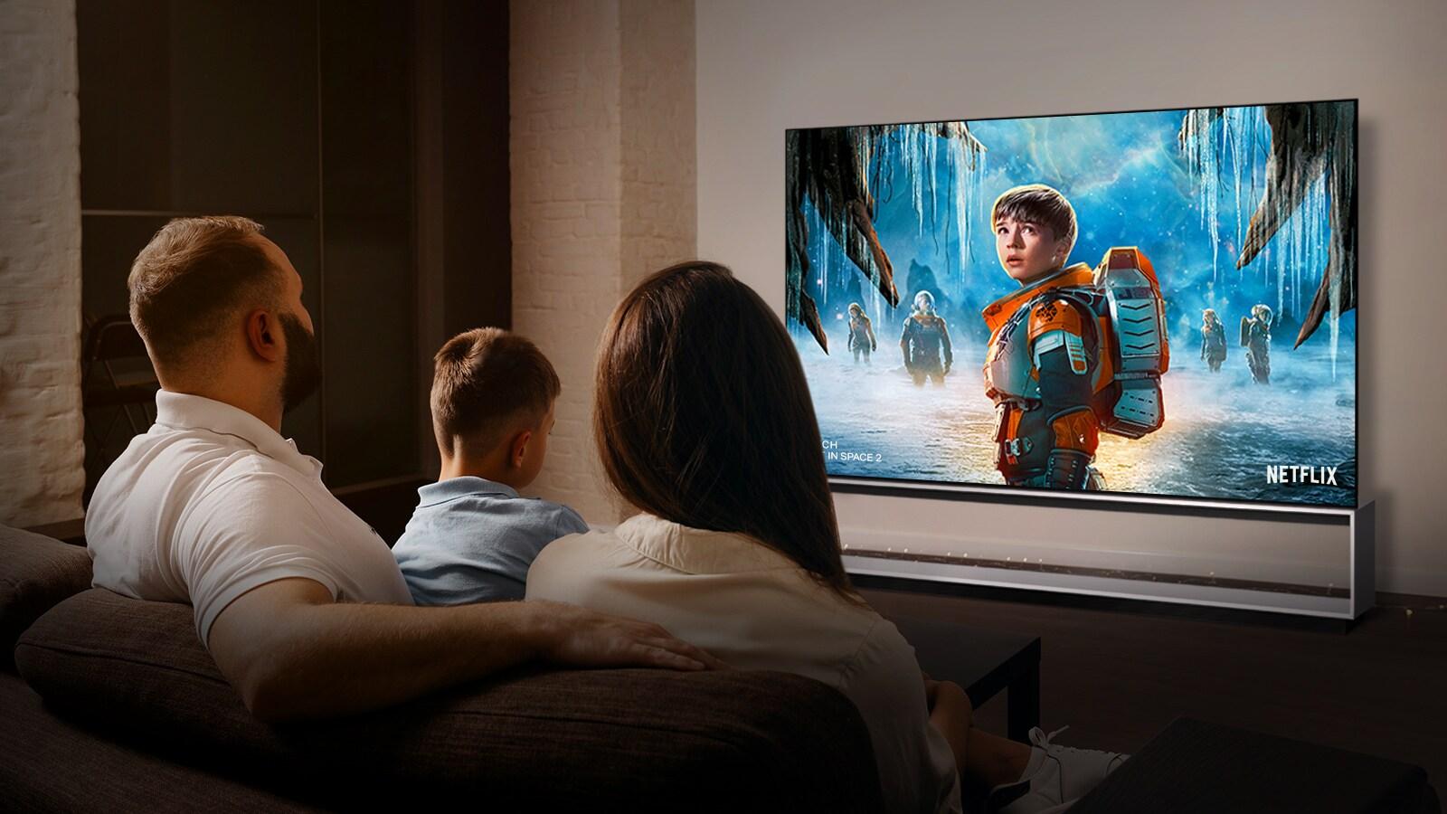 شريكان يجلسان على أريكة في غرفة النوم يشاهدان فيلمًا رومانسيًا على التلفزيون