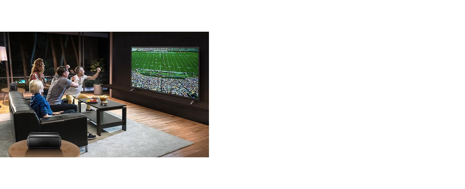 أناس يشاهدون الألعاب الرياضية على شاشة التلفزيون في غرفة المعيشة مع مكبرات صوت خلفية تعمل بتقنية البلوتوث.