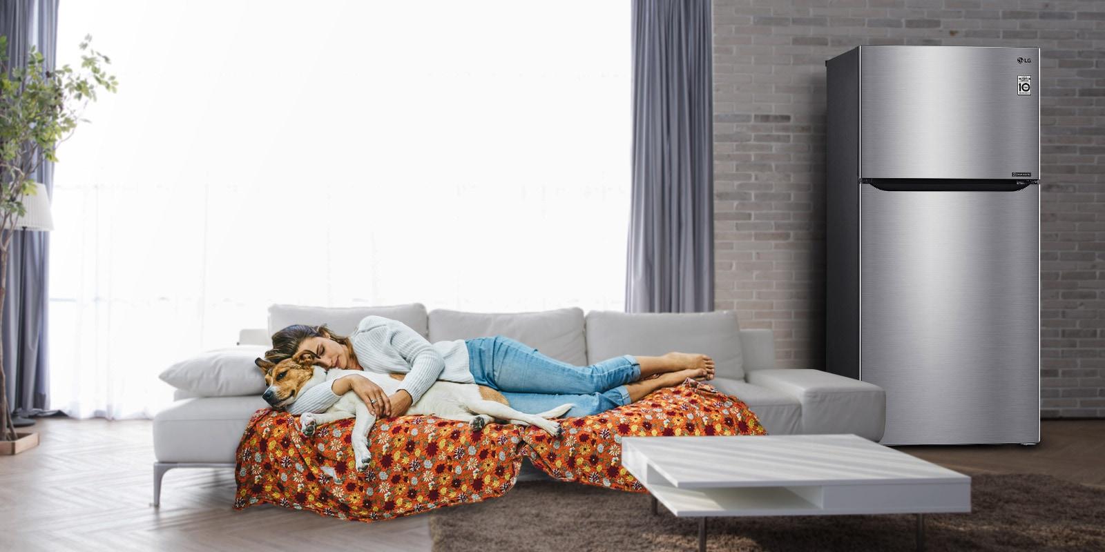 امرأة وكلب ينامان على أريكة بالقرب من الثلاجة.