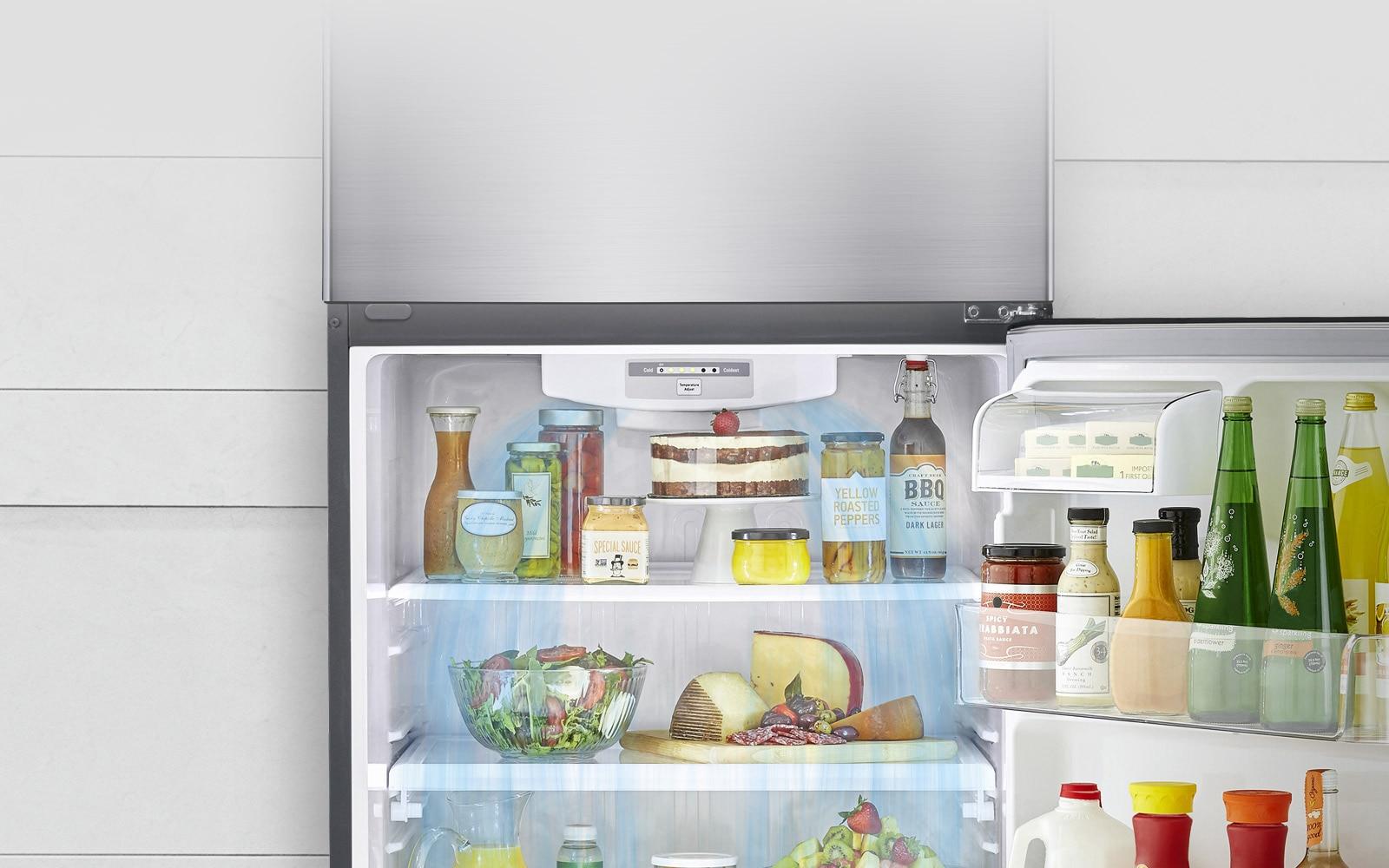 تظهر الثلاجة بالفريزر العلوي من إل جي مع فتح الباب السفلي. الثلاجة مليئة بالمنتجات ويظهر نظام التبريد الذي يطلق هواء التبريد الذي يدور من أعلى إلى أسفل الثلاجة.